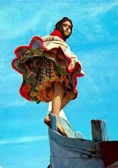 Mujer con traje típico que esta compuesto por siete faldas. Están en la placa vendiendo productos de la zona.