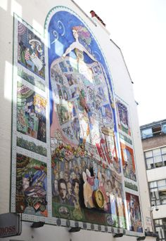 Spirit of Soho Mural, Broadwick Street.   Created by the Soho Community, completed in 1991 and restored in 2006. St Anne is shown looking over the people and places of Soho. Don't miss: When the clock strikes on the hour, watch actress and opera singer Theresa Cornelys wink at Casanova, while the bells chime.  #Carnaby #Art