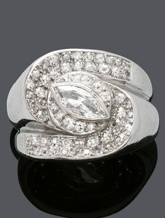 AN ART MODERNE DIAMOND RING, CIRCA 1935. Set at the centre with a marquise-shaped diamond weighing 0.70 ct, surrounded by circular-cut diamonds, mounted in platinum. #ArtModerne #Modernist #ring