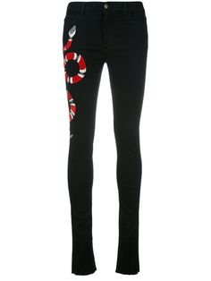 Shop Gucci snake embroidered skinny jeans.