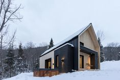 A steep gabled roof emerges from behind a snowy hill and blends in with the tightly clumped furry green pine trees surrounding it. The Villa Boreale is slowly revealed: a modern scandinavian-inspired cabin designed by Cargo Architecture for a young couple looking to nest in the frigid wilderness of Charlevoix, Quebec. Banks of snow nestle …
