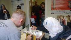 Visitors having a go at mending damaged books