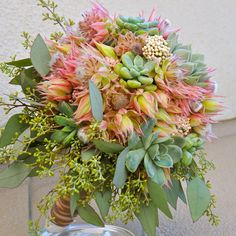 Blushing Bride Protea can be on the pink side like these or almost white in color. Flower Duet created this bouquet with succulents and seeded eucalyptus. Flowers by Flower Duet. Photo by Kit Wertz. #FinishWithFlowers