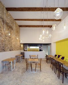 The main room features the regained outdated ceiling and the setting of a tension between gross side walls in stone and a pristine white wall in the middle of which a yellow alcove faces zelliges used for the midway panel of the bar, from which emerge the ten draft beer taps presented to the patrons on a monolithic white Corian countertop.