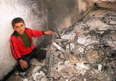 A handout picture released by the Higher Committee for the Syrian Revolution on April 11, 2012 shows a boy holding a burnt out bicycle in a house destroyed by violence in the town of Dael in the southern Syrian province of Daraa.