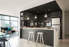 Black and white kitchen: gloss and matt black cabinets, white benchtops, island with waterfall edge, industrial wire cage pendant lights, dark tinted/smoked mirror splashback, white paint dipped wooden bar stools, neutral floor tiles