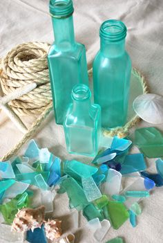How to paint clear glass bottles for that sea glass look:  Modge Podge or glue, neon food colorings, dish soap.  Spray with acrylic sealant.  Nice!