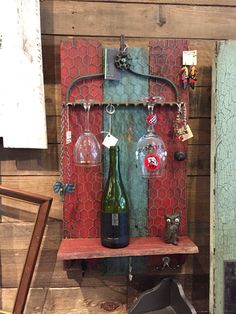 Wine Rack / jewelry display from pallets an old rake head,some chicken wire and old coat hooks
