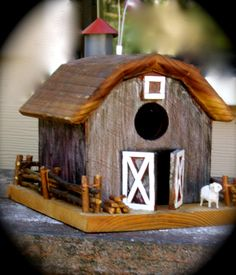This functional and decorative birdhouse is handmade by me, John Hope. I love to work with wood creating artistic and unique designs.    This is made of cedar and redwood. All of the parts are glued, nailed or screwed. I make my birdhouses with a removable bottom, for easy cleaning. They also have a built in hanger and all of the exterior surfaces are sealed for weather. All of the corners are mitered.    The fence, I handmade, using wood from my local trees. The barn doors act as a perch…