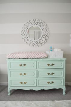 Mint green changing table/dresser in a girl's nursery with striped walls