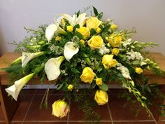 Elegant calla lilies grace this casket spray along with orchid sprays and