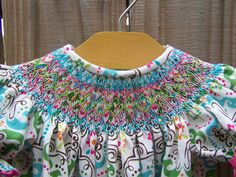 Like this geometric smocking=Bold waves of color on busy print is best.