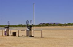 Two gas pumps, an empty road; Mount Conner looms in the distance;  Curtin Springs Station, Northern Territory, Australia.  January 2014.