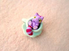 Tiny Cheshire Cat in a miniature tea cup by MijbilCreatures