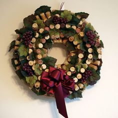 "The wreath measures 16"" in diameter. There is approximately 225 corks on the wreath. A toothpick is glued to each cork and then glued to a straw wreath. It is embellished with a burgundy satin bow and wine glass charms that I made with gold wire and glass beads, silk grapevine leaves, faux grapes, and gold charms. Wine Cork Wreath With Handmade Wine Glass Charms  etsy"
