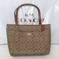 """COACH NWT Peyton Signature Tote (Khaki/Saddle) This is a BRAND NEW with tags 100% guaranteed authentic COACH Peyton signature tote in classic Khaki/Saddle. Pocket tote with gold tone hardware and coated canvas/leather trim. Durable, top-notch quality and very easy to clean (official coach care card included with bag)! Inside zip pocket; Zip-closure; Fabric lining. Leather hangtag. Outside open pocket with snap closure. Handles with 8 3/4 drop; Detachable strap with 19"""" drop included…"""