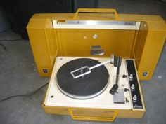 This might be the record player I had.  It was mustard yellow for sure and I loved it.
