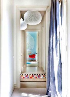 Long hallway featuring large round white pendant lights, a multicolored striped rug, a red chair, and wall map.