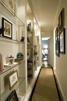 beige rug with black details, on laminate floor, near wall with glass shelves, containing artwork and decorations, long hallway runners, several framed images on opposite wall