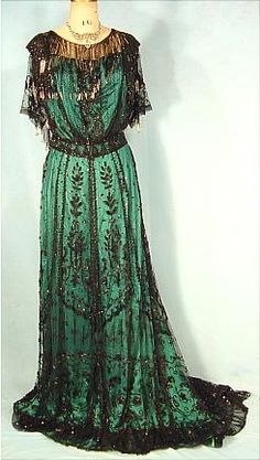 1907 Emerald turquoise green silk satin Edwardian gown. . Dripping with long silver and black bead fringe at neckline. Rounded train w/black net sew with seauins and bugle beads in stylized floral patters with runched chiffon band at hem.  McGrath label, San Francisco