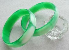 In unused condition; a lovely pair of vintage Moonglow Lucite bangle bracelets for Spring in green and white. Measures: EACH bracelet has a  2-1/2