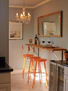 cuisine avec bar mural en bois brut, tabourets hauts en orange et lustre