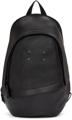 Structured grained leather backpack in black. Tonal textile trim throughout. Grosgrain carry handle at top. Adjustable shoulder straps. Signature stitch accent in white and zippered pocket at face. Two-way zip closure at main compartment. Zippered pocket at interior. Tonal stitching. Approx. 13.5 length x 16