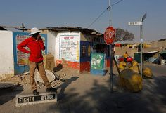 A man stands on the street sign for Eighth Avenue as he waits for a taxi in Alexandra Township Credit: Kim Ludbrook/EPA