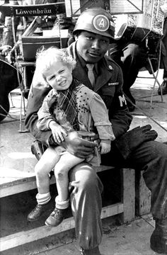 A U.S. Army MP (military policeman) holds a young German girl on his knee following the end of hostilities and the beginning of the Allied occupation of Germany. Munich, Bavaria, Germany. October...