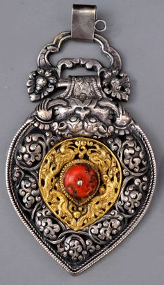 One of a pair of Tibetan belt ornaments, gilt silver , coral. 19th c.