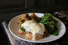 The eggs Florentine with wilted arugula and caramelized onions topped with a sharp cheddar Mornay sauce. Brunch at Rabbithole in NYC.