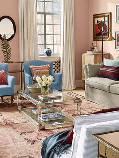 This sitting room is filled with natural light, further enhanced by the warm, pale pink walls. Character is added by mixing and clashing colours, patterns and textures.