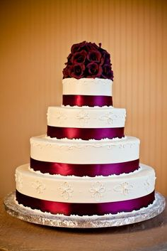 Wedding cake w/ ribbon and piping and flowers on top
