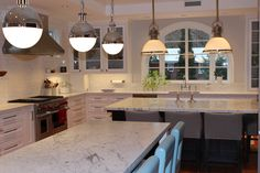 Double island kitchen countertops featuring light granite.