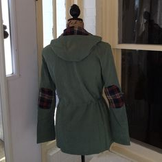 ⭐️HP⭐️ Olive & Plaid Jacket ⭐️NWT RETAIL⭐️ Cotton blend. Olive coat. Very thin. Spring jacket, not winter. Green, red, yellow, and cream plaid elbow patch and hood liner. Bronze buttons. Measurements: armpit to armpit- approx. 20 1/2 in.; arm length- approx. 23 1/2 in.; shoulder to shoulder- approx. 15 1/2 in.; shoulder to bottom hem- approx. 26 1/2 in. Cinch waist. PRICE IS FIRM! posh on first boutique Jackets & Coats Utility Jackets