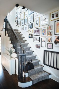 Photos line the wall along side a white staircase fitted with wood treads an a gray handrail complementing a gray stair runner. Stair Photo Walls, Picture Wall Staircase, Stairway Gallery Wall, Staircase Wall Decor, White Staircase, Stair Walls, Staircase Design, Gallery Walls, Black Stair Railing