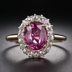 Antique Pink Sapphire and Diamond Ring.    A bright deep pink sapphire, weighing 2.50 carats, glistens from within a sparkling wreath of old mine-cut diamonds in this classic antique gemstone ring from the late Victorian period. Timeless. Lang Antiques.