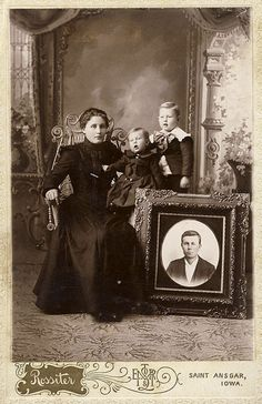 Photograph of a young widow with her two children and a portrait of her deceased husband .