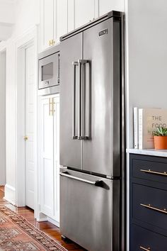 Blue and white kitchen fitted with white shaker cabinets accented with brass hardware boasts a pink kilim runner sat atop hardwood floors and an under cabinet double door, viking refrigerator positioned beside a built-in stainless steel microwave surrounded by cabinetry.