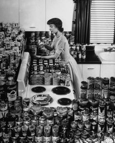 Hundreds of cans of assorted products stacked neatly on display in modern kitchen; young woman using the new approved can opener, 1952. Photo by Al Fenn / Time Life Pictures/Getty Images. °
