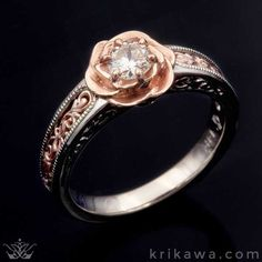 Feminine and floral with a vintage flair, the Vintage Scrollwork Rose Engagement Ring features an open, hand-carved band with intricate scrollwork. The solitaire stone you choose is nestled in a rose blossom. Design yours in the metals and center stone of your choice!