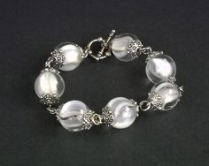 White cat's eye #marble bracelet.   The color is one of my favorite features of this bracelet. It features beautiful white and clear cat's eye marbles strung together with s... #bracelet #glass