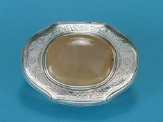 EARLY 18TH CENTURY SILVER & AGATE SNUFF BOX Probably English (George I / II), c1720-30, Unmarked. The cartouche-shaped lid over an oval body with concave sides, the whole with chased floral decoration   interspersed with panels of diapering within reeded rims, the cover inset with agate oval, gilt interior