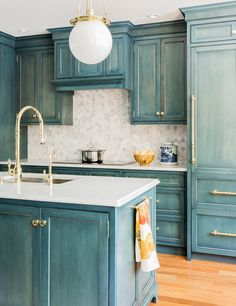 Blue kitchen, tiled backsplash, gold hardware in sink, industrial light fixture