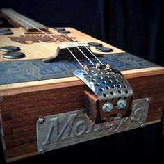 "Cigar Box Guitar - Undercrown box, bolt on maple neck and fretboard-24"" scale with zero fret. Acrylic paint, vinyl stencil for printing on back.  Sanded for aged appearance. Wood hummingbird bookmark attached with copper rivet on side. Vintage pie tin embossed with ""Monty's"" attached under veggie steamer tailpiece.  Tom Thompson - Primitive Acoustics"