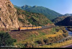 On a gorgeous spring morning in 1974, the Rio Grande Zephyr train #18 climbs Spanish Fork Canyon along it's namesake river approaching the small town of Thistle, Utah. The right of way at this point would be buried in mud in 1983 when a natural landslide blocked the D right of way, US Highway 6 and the Spanish Fork River. The railroad and highway would be relocated along the hillsides at right and a new spillway allowed the river to flow under the landslide.