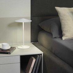 Lámpara de sobremesa Pla con iluminación LED integrada. Podrás regular la intensidad de luz. La parte interna está fabricada en policarbonato y la pantalla de metal, disponible en acabado lacado blanco texturado o gris antracita. Ideal para colocar como luz auxiliar en tu domitorio de estilo moderno.