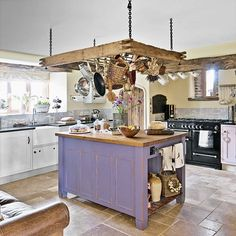 Country kitchen with purple storage island and pan rack