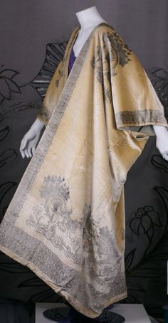 Fortuny translated the caftan as a loose fitting outer garment, usually made out of silk velvet crepe or gauze the fitted back and open front allowed for elaborate stenciled decoration and venetian bead trim. The hand stenciling is done with real silver metallic pigments aged to a mellow, burnished color.