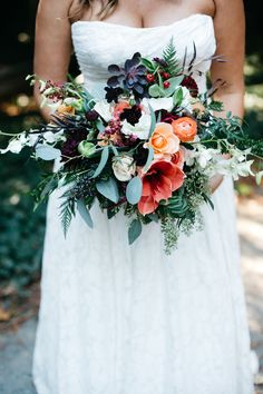 Fall bridal bouquet featuring coral amaryllis, ranunculus, garden roses, burgundy dahlia, smoke bush, eucaulyptus, dendrobium orchid, chocolate cosmos, ferns and more. Flowers by Lily + Mint. www.lilyandmint.com. Photo by Studio 13 Designs.